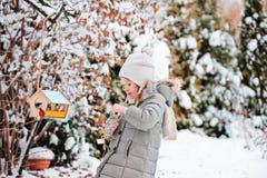 La muchacha del niño pone las semillas en alimentador del pájaro en jardín nevoso del invierno Fotos de archivo