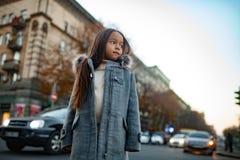 La muchacha del niño se está colocando en la acera en el fondo del str de la ciudad fotografía de archivo libre de regalías