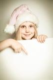 La muchacha del niño se vistió en el sombrero de Papá Noel con el espacio en blanco de papel Imagenes de archivo