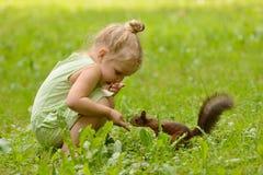 La muchacha del niño alimenta la ardilla Imágenes de archivo libres de regalías
