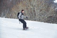 La muchacha del novato está aprendiendo esquiar con la snowboard Foto de archivo