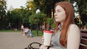 La muchacha del pelirrojo bebe el café en el parque almacen de video