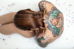 La muchacha del pelirrojo con el pelo mojado se sienta en el baño por completo del agua con m imagenes de archivo