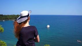 La muchacha del pelirrojo mira de una colina en el mar Mediterráneo con un yate en Phaselis Ciudad de Lycia antiguo Turqu?a almacen de video