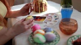 La muchacha del pelirrojo pinta los huevos de Pascua con un cepillo en la torta de Pascua de la tabla, huevos, dulces, ramo de fl almacen de video