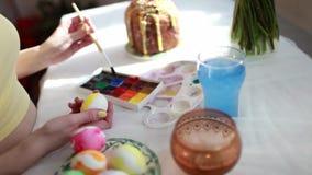 La muchacha del pelirrojo pinta los huevos de Pascua con un cepillo en la torta de Pascua de la tabla, huevos, dulces, ramo de fl metrajes