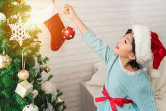 La muchacha del pequeño niño está adornando el árbol de navidad Imágenes de archivo libres de regalías