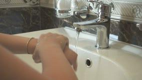La muchacha del pequeño niño se lava las manos con la pulsera de oro metrajes