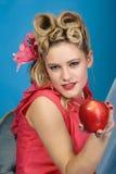 La muchacha del pinup de los años '50 le tienta con una manzana Foto de archivo libre de regalías