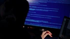 La muchacha del pirata informático trabaja en el ordenador metrajes