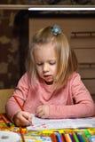 La muchacha del preescolar del niño aprende extraer y escribir en cuadernos en casa por la tarde bajo luz de una lámpara de escri imagen de archivo libre de regalías