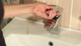 La muchacha del primer abre el grifo de agua en cuarto de baño almacen de video