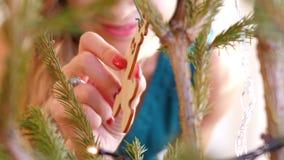 La muchacha del primer de la cámara lenta toca el conejo en el árbol de navidad almacen de metraje de vídeo