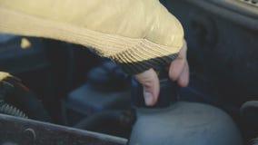 La muchacha del primer desatornilla la tapa de un tanque con el líquido debajo de la capilla de su coche Mantenimiento del coche almacen de video