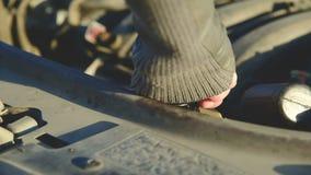 La muchacha del primer desatornilla la tapa de un tanque con el líquido debajo de la capilla de su coche Mantenimiento del coche metrajes