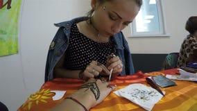 La muchacha del primer dibuja los modelos de Oriente con alheña en la mano del cliente libre illustration