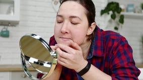 La muchacha del primer examina la piel facial en el espejo en cocina metrajes