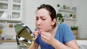La muchacha del primer hace estallar zits en piel facial en el espejo en cocina metrajes