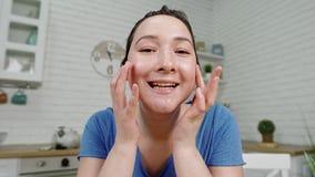 La muchacha del primer hace masaje facial con los fingeres en el espejo almacen de metraje de vídeo