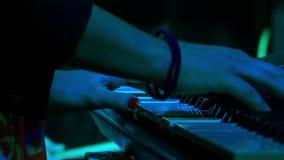 La muchacha del primer juega el piano en barra de la noche bajo flashes ligeros almacen de metraje de vídeo