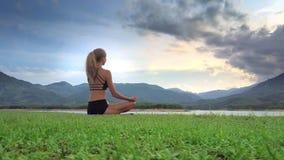 La muchacha del primer medita en la actitud Lotus de la yoga contra Hilly Land