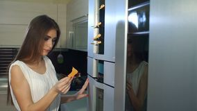 La muchacha del primer toma una nota de la puerta del refrigerador Cámara lenta almacen de video
