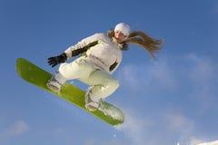 La muchacha del Snowboard salta Imagen de archivo libre de regalías