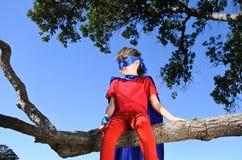 La muchacha del super héroe se sienta en un árbol foto de archivo libre de regalías