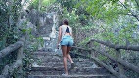 La muchacha del tiro del ángulo bajo en pantalones cortos va encima de los pasos de piedra en la colina almacen de metraje de vídeo