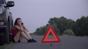 La muchacha del trastorno cerca de su coche arruinado que la mujer joven se está sentando cerca de mujer quebrada del coche está  metrajes