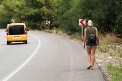 La muchacha del verano en pantalones cortos cortos camina en el lado de una carretera de asfalto imagenes de archivo