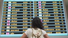 La muchacha del viaje mira el tablero del aeropuerto metrajes
