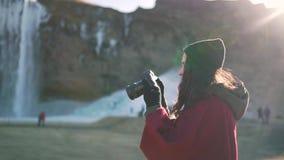 La muchacha del viaje mira las fotos en la cámara almacen de metraje de vídeo
