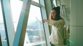 La muchacha del viaje se coloca en la ventana en terminal de aeropuerto almacen de metraje de vídeo