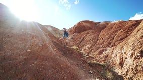 La muchacha del viajero en pantalones cortos y casquillo con una mochila se está colocando en un pico de montaña rojo en los rayo almacen de metraje de vídeo