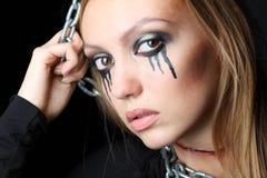 La muchacha del zombi con negro rasga y la garganta del corte cuelga en encadenamiento foto de archivo