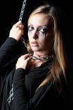 La muchacha del zombi con negro rasga y la garganta del corte se aferra encadenamiento del metal Foto de archivo libre de regalías
