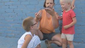 La muchacha delgada con los niños cogió el polluelo del gorrión y lo miraba en sus brazos almacen de metraje de vídeo