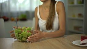 La muchacha delgada elige la ensalada en vez de la torta, dieta equilibrada sana, autodisciplina almacen de video