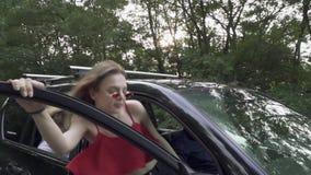 La muchacha delgada en camisa y vidrios rojos se sienta en la compañía de automóviles negra grande de tres personas está viajando almacen de metraje de vídeo
