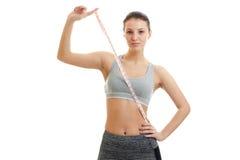 La muchacha delgada en ropa de deportes se levanta recta y manos en las manos de la cinta métrica Fotos de archivo libres de regalías