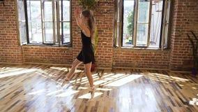 La muchacha delgada encantadora en cuerpo negro y falda realiza un salto del ballet clásico en el estudio del diseño del desván b almacen de video