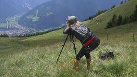 La muchacha delgada fotografía las montañas en una DSLR-cámara almacen de metraje de vídeo
