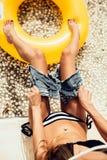 La muchacha delgada hermosa en bikini rayado atractivo quita sus pantalones cortos Imágenes de archivo libres de regalías