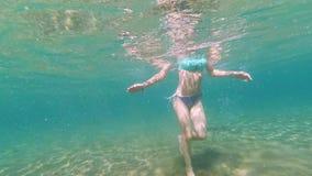 La muchacha delgada joven aprende nadar en la playa en el verano de vacaciones almacen de metraje de vídeo