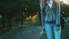 La muchacha delgada joven con la mochila y los auriculares camina alrededor de la ciudad almacen de video