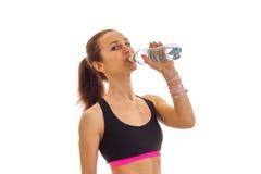 La muchacha delgada joven en top del negro bebe el agua de una botella Imagen de archivo