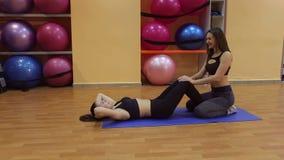 La muchacha delgada joven sacude los músculos abdominales con el instructor personal almacen de video