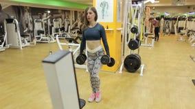 La muchacha delgada joven se pone en cuclillas y hace estocadas con pesas de gimnasia en el gimnasio almacen de video