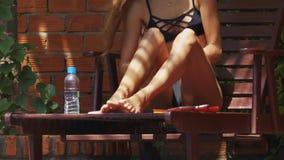 La muchacha delgada mancha las piernas y los muslos con la protección solar